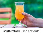male hand holding a glass of... | Shutterstock . vector #1144792034