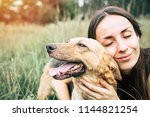 Stock photo portrait of a young cute woman with her beautiful dog lying outdoors in park shelter dog and 1144821254
