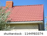 house with red metal roof and... | Shutterstock . vector #1144983374