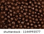 Small photo of Chocolate dragee. Dark brown chocolate dragee, hazelnut Beans. full frame background. traditional sweets. texture for design.