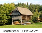 Small photo of Tall wooden barn outdoor building with open lower part for storage surrounded with uncut grass, large pine trees and other vegetation on warm sunny day