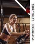 positive beautiful fit woman is ... | Shutterstock . vector #1145105081