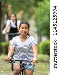 asian teenager riding a bicycle ... | Shutterstock . vector #1145125994