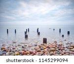 wooden breakwater in peaceful... | Shutterstock . vector #1145299094