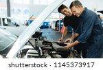 two happy automobile mechanics... | Shutterstock . vector #1145373917