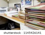 desk piles up with files and... | Shutterstock . vector #1145426141