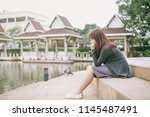 asian woman sitting alone and... | Shutterstock . vector #1145487491