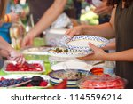 people filling plates at a... | Shutterstock . vector #1145596214