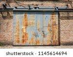 sliding the rusty iron gate... | Shutterstock . vector #1145614694