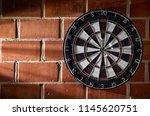 Stock photo dartboard on a brick wall darts in the bullseye bullseye 1145620751