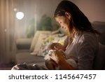 Small photo of Young beautiful mother, breastfeeding her newborn baby boy at night, dim light. Mom breastfeeding infant