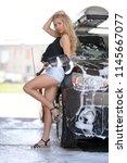 a blonde woman washing a suv car | Shutterstock . vector #1145667077