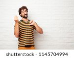 young dumb man looking happy ... | Shutterstock . vector #1145704994