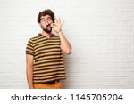"young dumb man gesturing ""zip... 