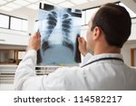 Doctor studying x-ray in hopsital hallway, Healthcare workers in the Coronavirus Covid19 pandemic - stock photo