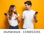 Small photo of Photo of discontent man and woman looking at each other with perplexity while holding mobile phones isolated over yellow background