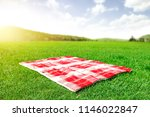 red and white blanket on green... | Shutterstock . vector #1146022847