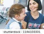 smiling mother looking at... | Shutterstock . vector #1146103331