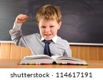 Confident elementary aged schoolboy sitting at the desk - stock photo