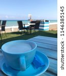 Blue cup and saucer with frothy Latte and a beachside view. Sugar sachet in the saucer. - stock photo