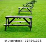 Row of empty picnic tables on a grass - stock photo