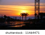 Sunset on a beach (with a construction site for a new hotel in the foreground) - stock photo