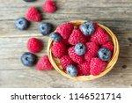 raspberries and blueberries in... | Shutterstock . vector #1146521714