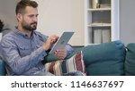 man browsing internet on tablet ... | Shutterstock . vector #1146637697