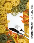 Note paper on various Italian pasta background and silverware - stock photo