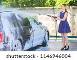pretty girl washes a car in a... | Shutterstock . vector #1146946004