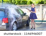 pretty girl washes a car in a... | Shutterstock . vector #1146946007
