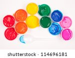 motley paints on the white background. paints arranged as rainbow with plastic spoon partly colored in blue paint. studio shot - stock photo