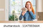 redhead woman holding dollar... | Shutterstock . vector #1147003664
