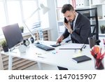 a man is sitting at the desk at ... | Shutterstock . vector #1147015907