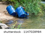 dumped blue oil drums cause... | Shutterstock . vector #1147028984