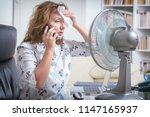 Small photo of Woman suffers from heat while working in the office and tries to cool off by the fan