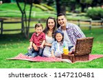 beautiful family in a picnic at ... | Shutterstock . vector #1147210481