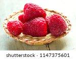raspberries  in a basket on a... | Shutterstock . vector #1147375601