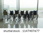 wheelchair by the glass window... | Shutterstock . vector #1147407677