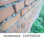 wall of red brick. green grass. ... | Shutterstock . vector #1147510151