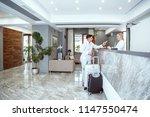 Stock photo couple near reception desk in hotel 1147550474