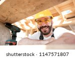 The man is a builder on the roof of a wooden frame house. - stock photo