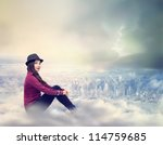 Happy Young Woman Sitting on the Clouds Above the City - stock photo