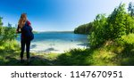 hiker stands on the green coast ... | Shutterstock . vector #1147670951
