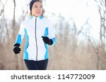 Running young Asian woman jogging in a winter fleece and gloves in open countryside with copyspace in a health and fitness concept - stock photo
