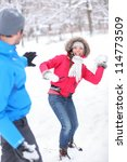 Young couple playing in the snow in snowball fight with a vivacious smiling Asian girl taking aim at her husband with a snowball - stock photo