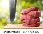 raw meat slices and knife on... | Shutterstock . vector #1147735127