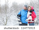Young interracial couple in winter carrying ice skates standing close together looking out over a snowy winter landscape with copyspace. Asian woman, Caucasian man. - stock photo