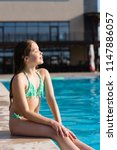 teenage girl posing near pool | Shutterstock . vector #1147886057