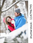 Romantic young couple holding each other in a close embrace and laughing merrily hugging in the snow - stock photo